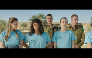 A group of young women in blue t shirts stand in front of two Israeli soldiers.
