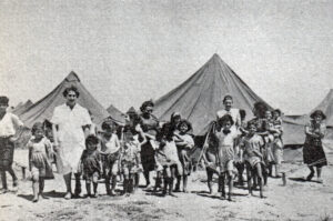 A group of children and adults stand in front of tents on sand