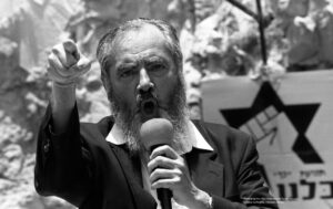 Rabbi Meir Kahane yells into a mic with his finger in the air