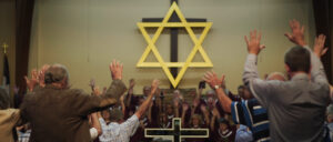 A group of people pray with their arms up. Above them there is a large Star of David.