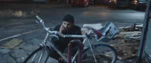 A man squats next to a locked bicycle. He is also on the phone.