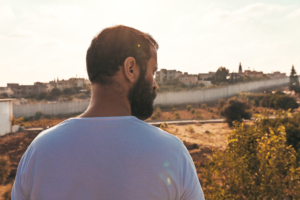 A man with a beard and a white-tshirt faces a field and the Israeli border wall.