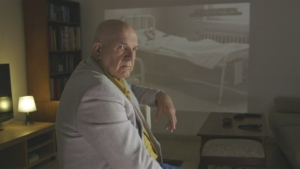 A bald man in a grey suit jacket turns around in his chair looking away from a projected image on a wall of a man covered in bandages in a bed.