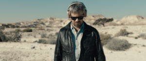 A man wearing a black leather jacket, sunglasses, and large over-ear headphones stands in the desert.