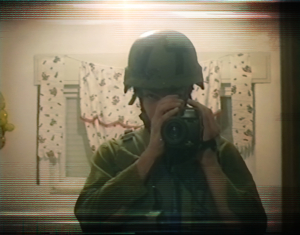 A male soldier wearing his gear and a helmet films himself with a camcorder in a mirror.