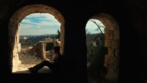 A woman sits in a shaded archway looking out over a valley