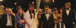 A bride and groom stand in front of a crowd of people