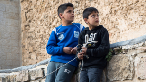 Two young boys stand against a stone wall, holding a rope.