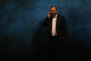 Ehud Barak stands in front of a blue background talking on a cell phone.