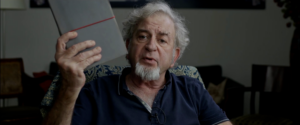 A man with a beard sits and holds a book up to the camera.